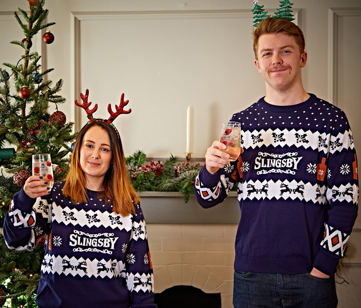 A couple wearing Slingsby Gin Christmas jumpers
